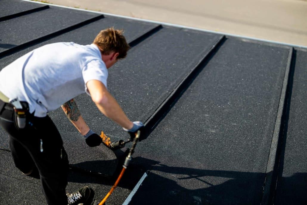 Medarbejder laver listedækning tagpap på tag